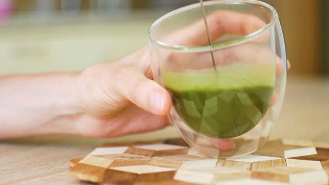 weibliche hände halten doppelglas mit heißen grünen tee matcha latte und fügen sie mehr getränk auf die tasse. detox- und gesunde ernährungskonzepte - milchkaffee stock-videos und b-roll-filmmaterial