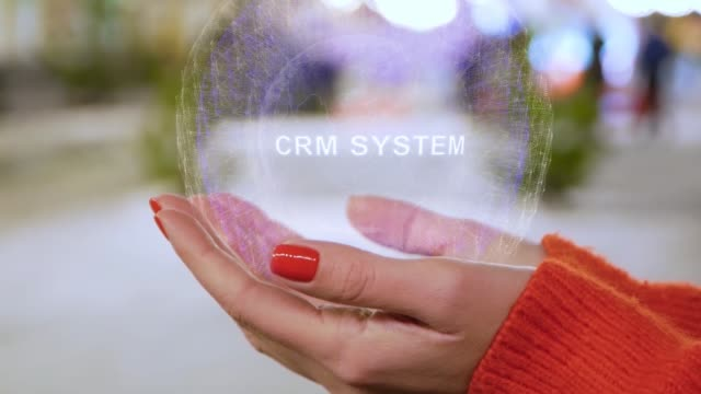 Female hands holding hologram with text CRM system