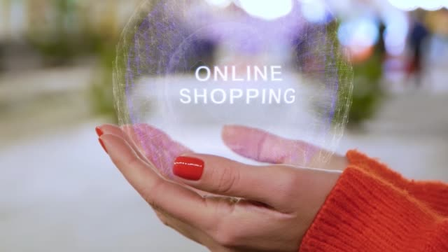 Female hands holding hologram with text Online shopping