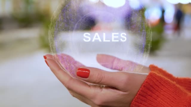 Female hands holding hologram with text Sales target