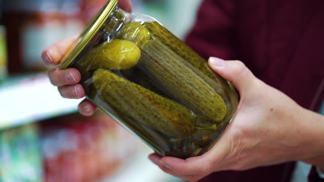 Female hands holding jar of pickled cucumbers in supermarket Female hands holding glass jar of pickled cucumbers, supermarket shelves on blurred background. Closeup of woman buying food. Concept of shopping pickle stock videos & royalty-free footage
