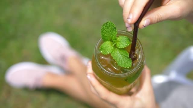 vídeos de stock, filmes e b-roll de mãos fêmeas que prendem a bebida fresca do verão com hortelã - tea drinks