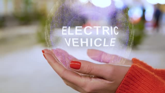 Female hands holding text Electric Vehicle