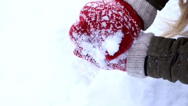 Female hands in knitted mittens making snowball video