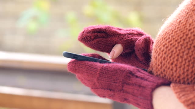 Female hands in mittens using smart phone. video