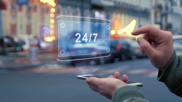 Female hands interact HUD hologram 24 7 Female hands on the street interact with a HUD hologram with text 24 7. Woman uses the holographic technology of the future in the smartphone screen on the background of the evening city hologram stock videos & royalty-free footage