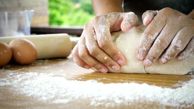 Female hands kneading dough in flour with green tree blurred background video