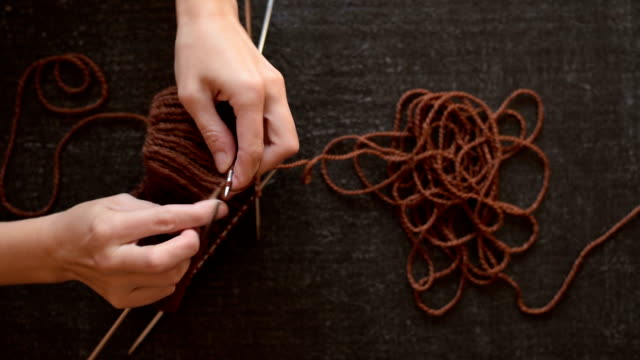 Female hands knitting brown yarn video