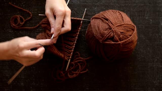 Female hands knitting on black background video