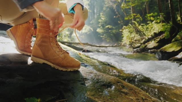 vidéos et rushes de les mains femelles lacent la femelle sur une botte de trekking dans la forêt. en arrière-plan, une rivière de montagne et les rayons du soleil brillent à travers les branches des arbres - bottes