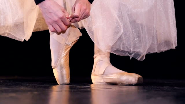 Female hands lace up two ribbons on ballet shoes. video