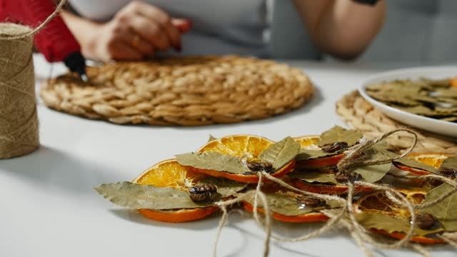 Female hands make christmas decoration from dried orange use glue gun.