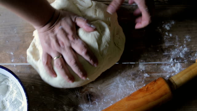 female hands making bread dough on wooden table - impasto video stock e b–roll