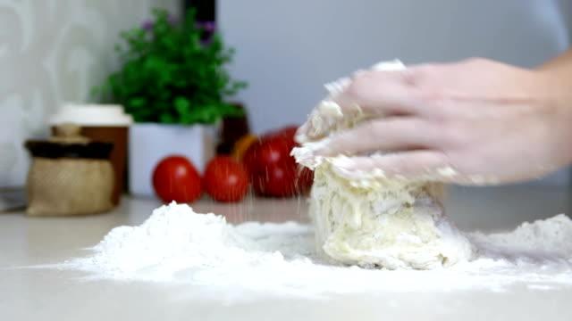 vídeos de stock, filmes e b-roll de mãos femininas fazendo massa para pizza ou pão na cozinha. mulher amassando massa na mesa. - comida salgada