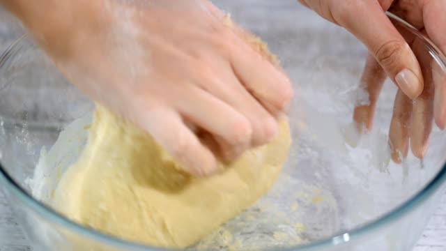 Female hands making dough in the glass bowl.