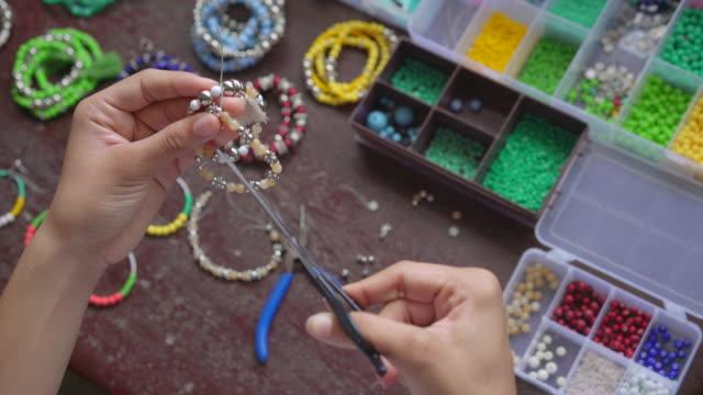vidéos et rushes de female hands making handmade bijouterie with little balls and stones - joaillerie