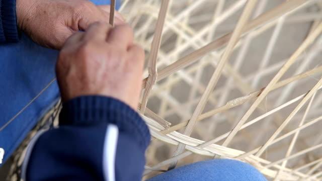 kvinna händer manuellt vävning bambu korg. kvinnan gör handgjord korg - halmslöjd bildbanksvideor och videomaterial från bakom kulisserna