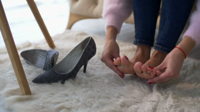 Female hands massaging tired aching feet at home Closeup of female hands massaging tired aching feet in domestic room with high heel shoes lying near. Exhauted businesswoman giving herself foot massage at home after wearing high heels all day long. foot stock videos & royalty-free footage