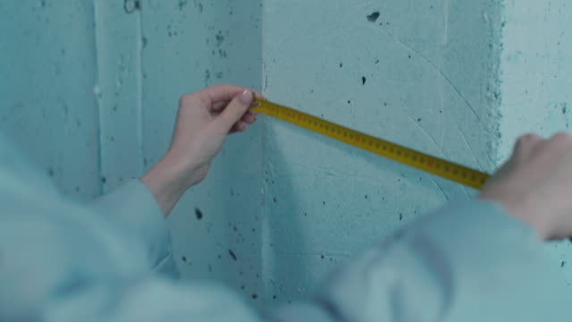 female hands measuring basement wall with tape - длина стоковые видео и кадры b-roll