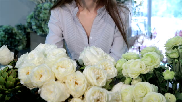 Female hands moves white roses at flower shop video