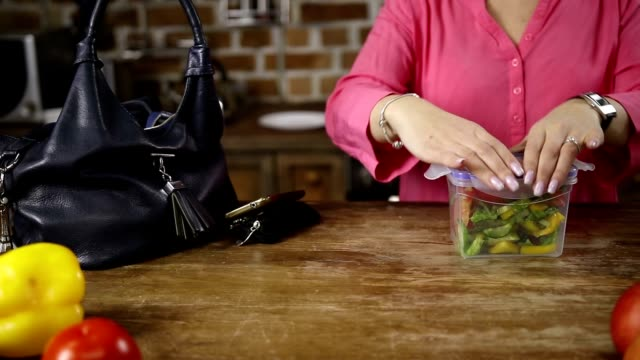 Female hands packing lunch into bag in kitchen