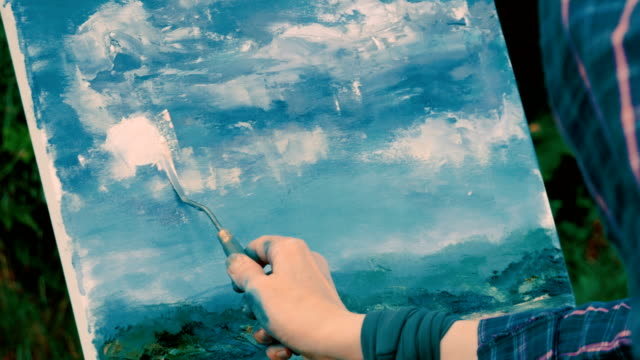 female hands painting a water landscape with oil paints using palette knife. 4k - cavalletto attrezzatura per arti e mestieri video stock e b–roll