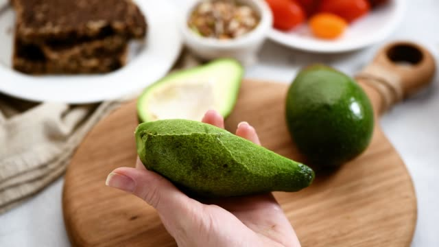 Female hands peeling avocado Time lapse of female hands peeling avocado closeup view. Healthy vegan vegetarian food concept, clean eating diet fat nutrient stock videos & royalty-free footage