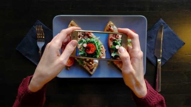 vídeos y material grabado en eventos de stock de manos femeninas fotografiando comida apetitoso por teléfono inteligente en el restaurante. 4k. deliciosos gofres frescos con espinacas y tomates cherry listos en la cafetería. - gastronomía fina