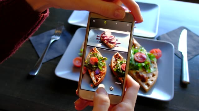 female hands photographing appetizing food by smartphone in the restaurant. 4k. delicious fresh waffles with spinach and cherry tomatoes ready in cafe. - jedzenie wegetariańskie filmów i materiałów b-roll
