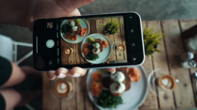Female hands photographing appetizing food by smartphone in the restaurant. Traditional breakfast in Bali Indonesia
