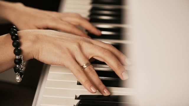female hands playing piano. woman touches fingers on keys. close up - браслет стоковые видео и кадры b-roll