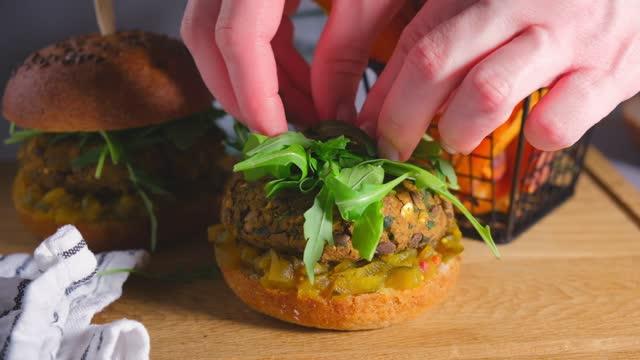 女性の手は、木製のボード上の野菜、ルッコラ、マスタードソースとビーガンレンズ豆バーガーを準備します。 - ベジタリアン料理点の映像素材/bロール
