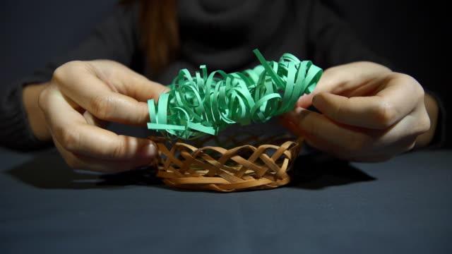 kvinnliga händer sätta i en bambu korg skivad från grönbok gräs. - halmslöjd bildbanksvideor och videomaterial från bakom kulisserna