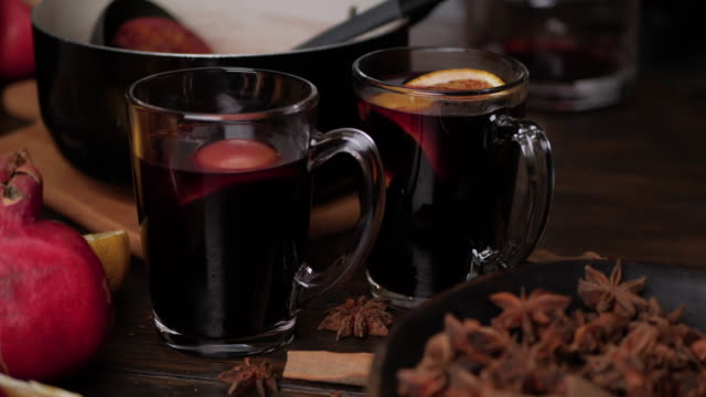 Female hands put slices of oranges and anise stars in clear glass mugs with mulled wine. Close up slider movement.