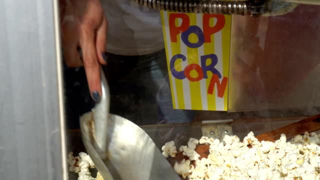 weibliche hände steckt popcorn in papiertüte. verkauf von popcorn auf der straße. gimbal erschossen - handvoll stock-videos und b-roll-filmmaterial