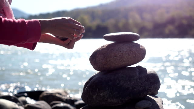 Female hands putting pebble stack next to the mountain river in slow motion. 3840x2160 video