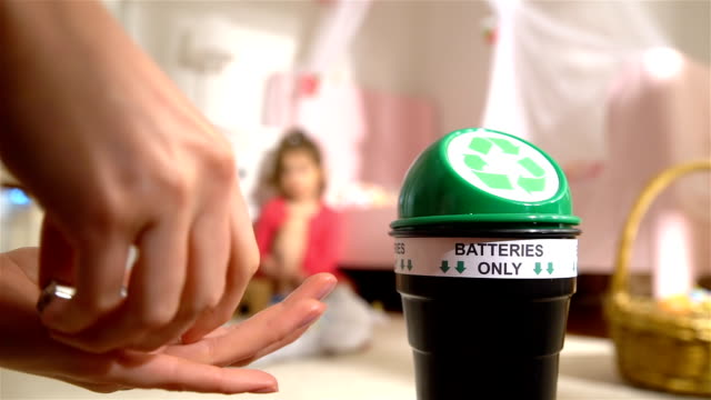 vídeos de stock e filmes b-roll de female hands putting used batteries into special recycling box at home. child playing on the background. batteries only. slow motion - box separate life