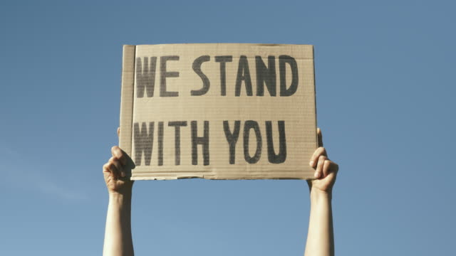 """kvinnliga händer höjer upp skylten vi står med dig mot blå himmel. kvinnan har affischen """"we stand with you"""". svarta liv betyder fredlig protest. demonstrationer mot polisbrutalitet och anti-svart rasism - etnicitet bildbanksvideor och videomaterial från bakom kulisserna"""