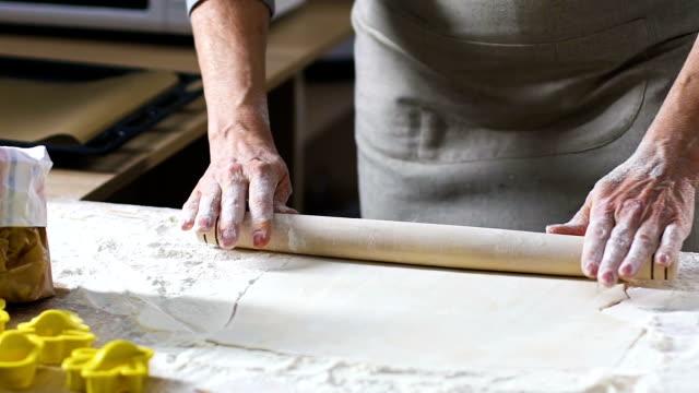 女性の手ロール圧延ピンと生地を小麦粉で覆われた木製のテーブルに - 自家製点の映像素材/bロール