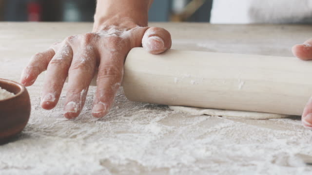 female hands rolling dough on wooden table - impasto video stock e b–roll