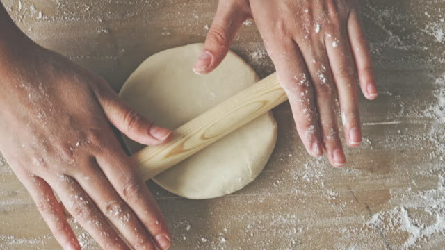 Female hands rolling dough on wooden table Female hands rolling dough on wooden table dough stock videos & royalty-free footage