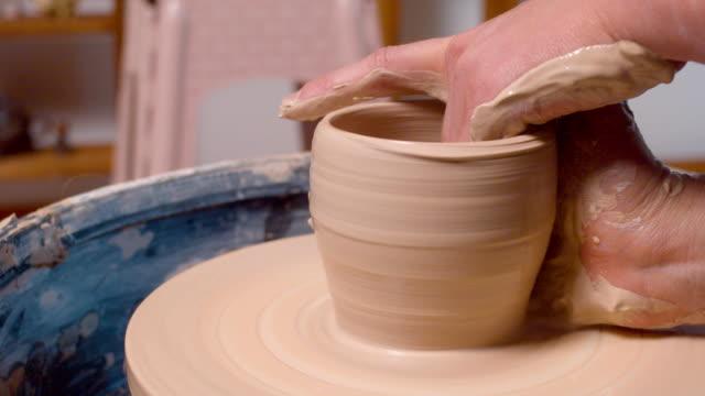 Female hands sculpting a pot.