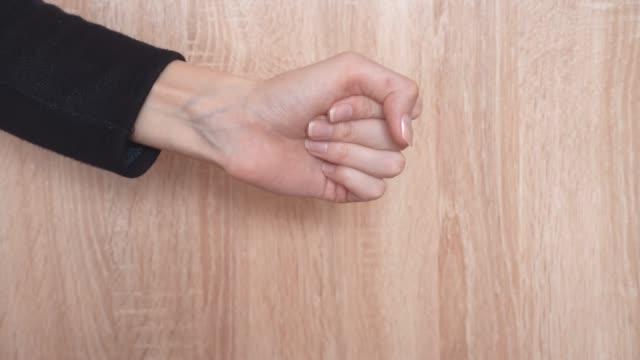 vídeos y material grabado en eventos de stock de las manos femeninas muestran tijeras de papel de roca sobre un fondo claro - espalda humana