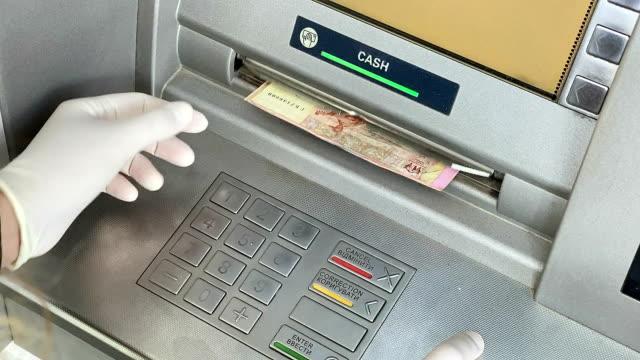 vídeos de stock, filmes e b-roll de mãos femininas pegam dinheiro de um caixa eletrônico. - ucrânia