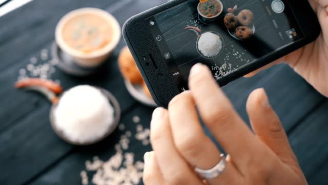 vídeos de stock e filmes b-roll de female hands take photos of indian food by smartphone. closeup. 4k. - fotografar
