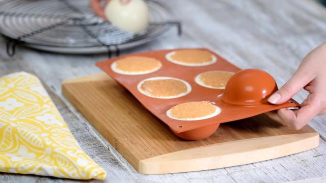 vídeos de stock e filmes b-roll de female hands taking square mousse cakes out of a flexible silicone mold, close-up. - utensílio