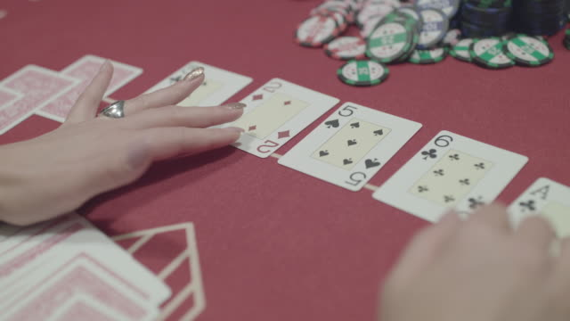 Female hands touch the cards laid out on the table while playing poker video