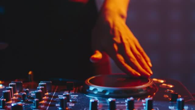 vídeos de stock, filmes e b-roll de mãos femininas girando botões de dj mixer - dj