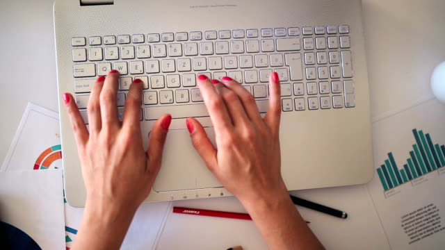 Female hands typing laptop computer keyboard, top view video