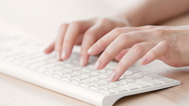 Female hands typing on a white keyboard